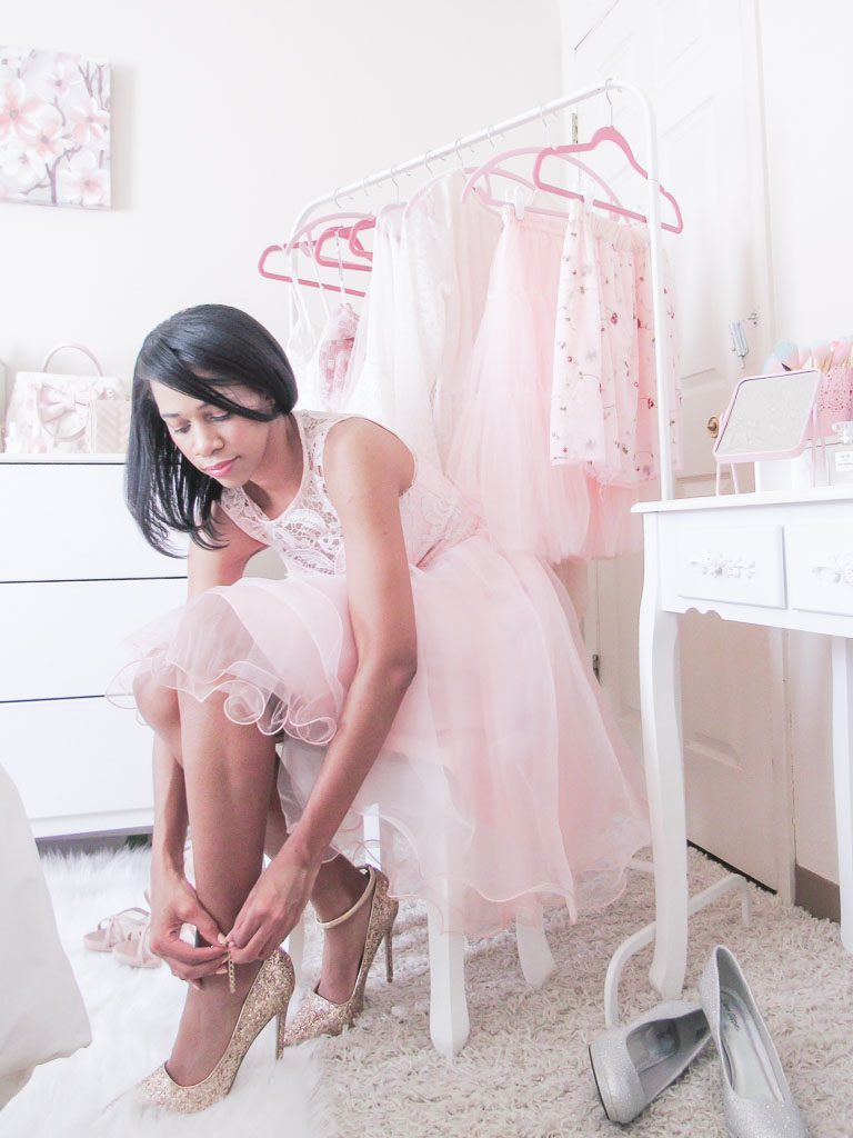 Woman sitting on a stool wearing a pink dress putting on gold shoes