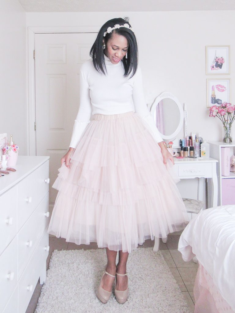 Woman wearing a pink tulle skirt and white sweater.