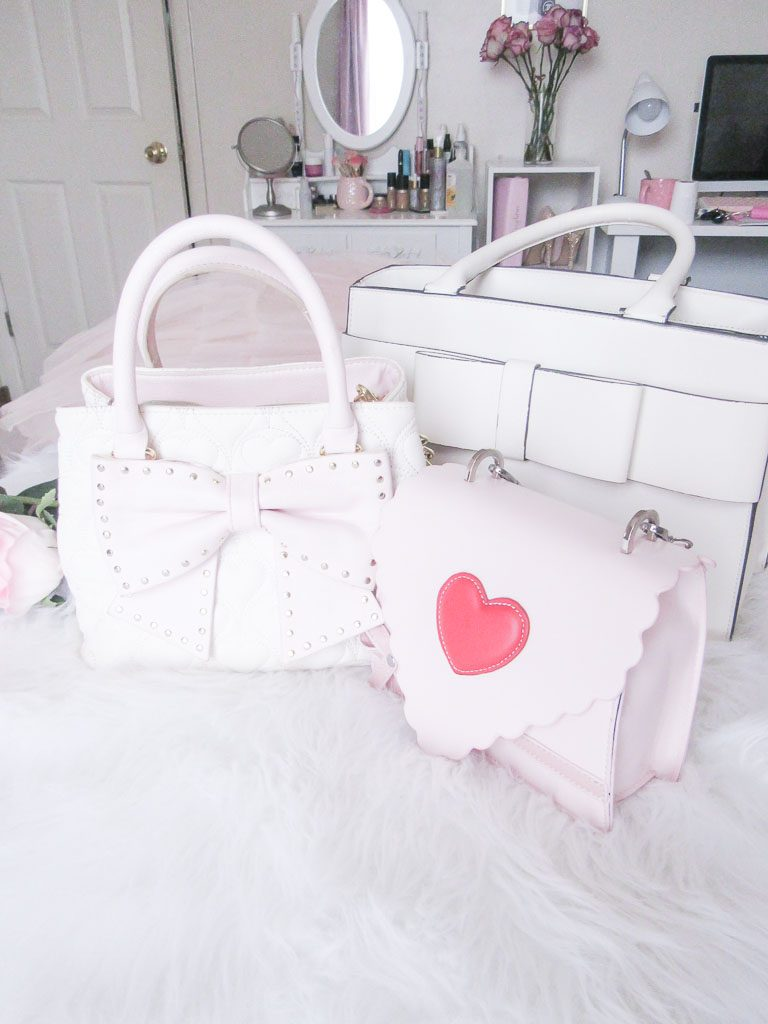 Pink and white handbags on a white bed.