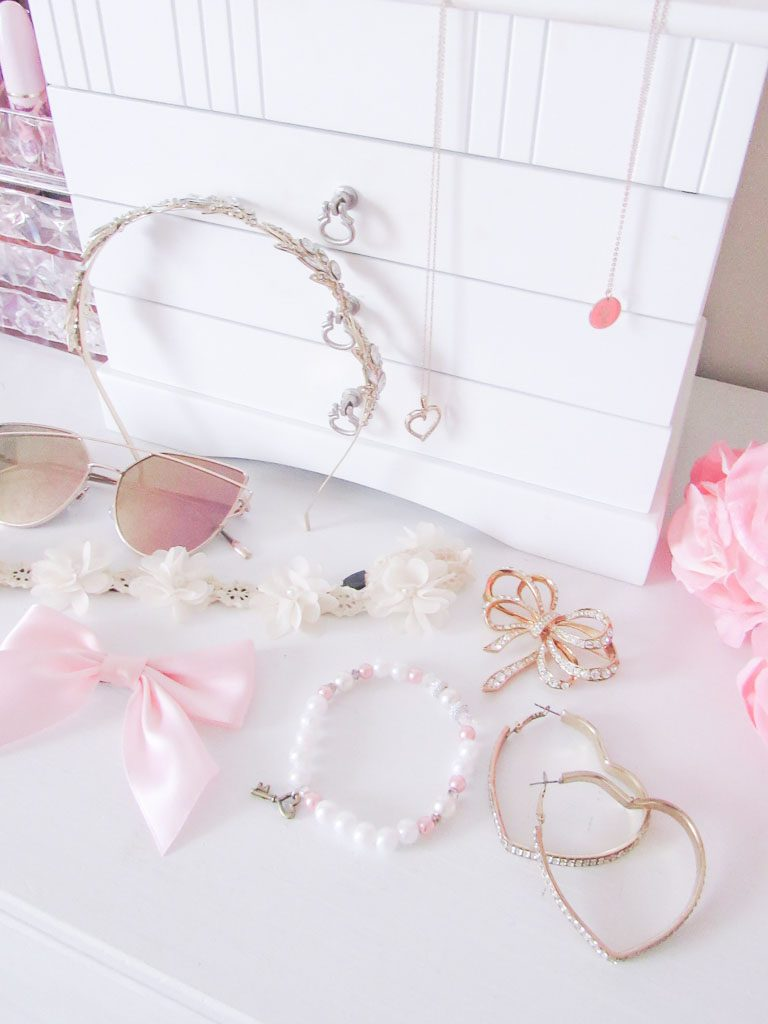 Feminine wardrobe accessories on a white dresser.