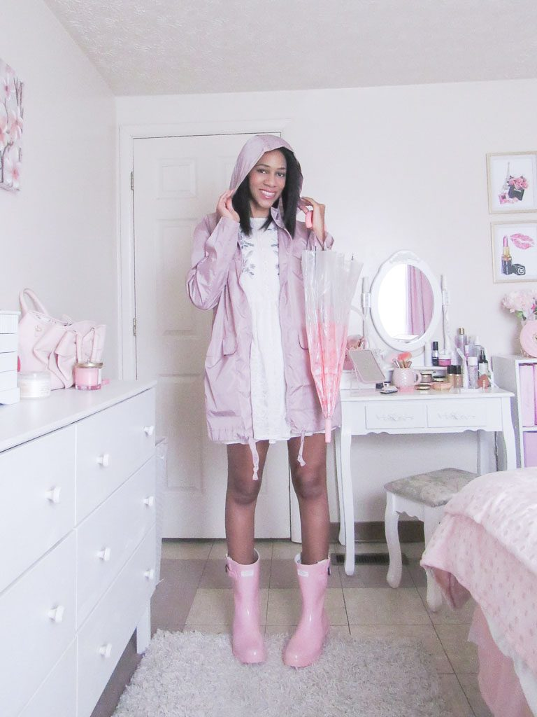 woman wearing pink rain jacket and rain boots in a white bedroom
