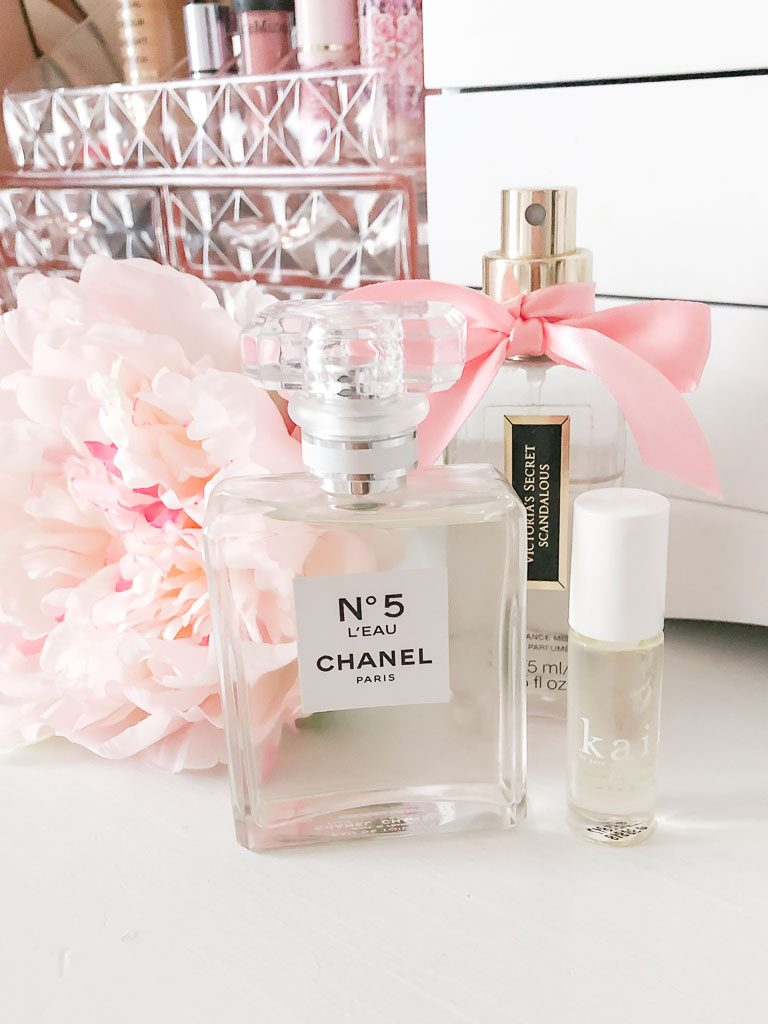 Perfume sitting on a white dresser with a pink peony.