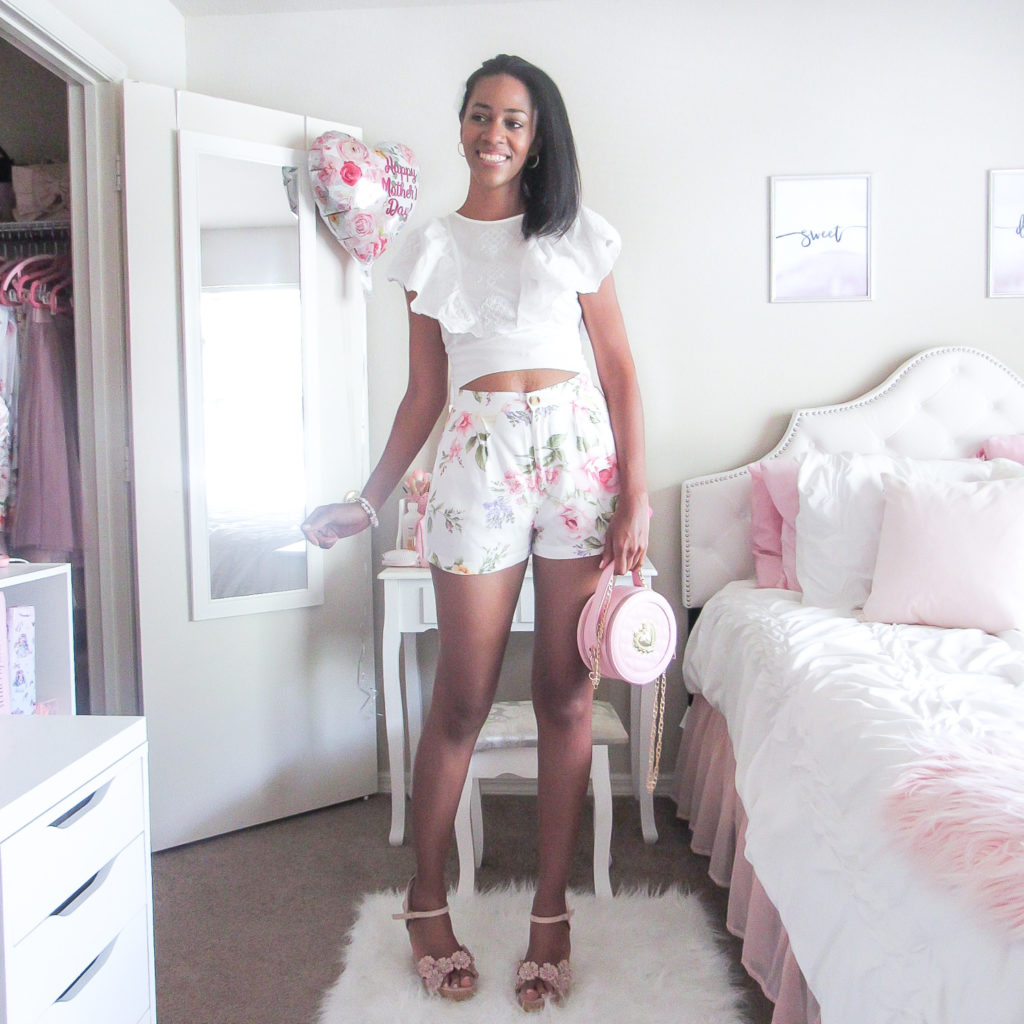 Woman wearing floral shorts and a white blouse